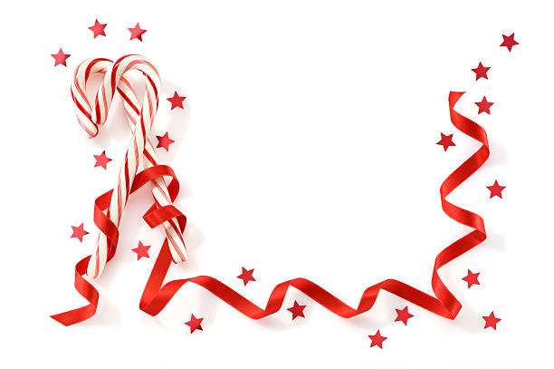 Greeting Card With Candy Canes Ribbon And Confetti.Color Image Two candy canes wrapped in a red ribbon with confetti on a white background. candy cane stock pictures, royalty-free photos & images