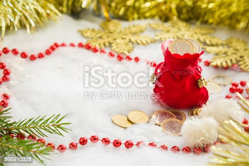 istock Greeting card with decorative Christmas accessories and red Santa Claus sack with euro coins. Mock up for money gift and seasonal offers as advertising or other ideas. Empty place for a text. 866910328