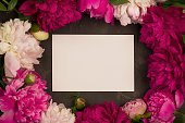 istock Greeting card with peony flowers on plaster background. 990529620