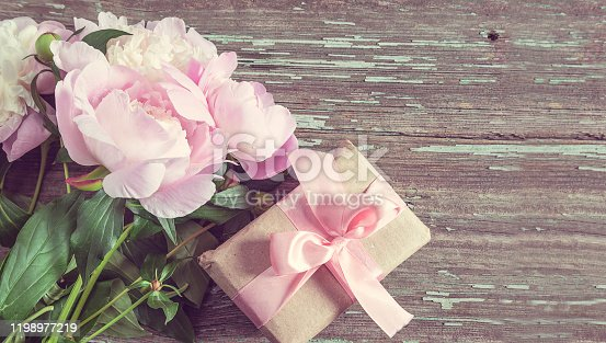 Beautiful bouquet of pink and white peonies on rustic wooden background