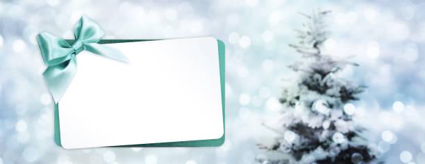 gruß geschenkkarte mit grüner schleife isoliert auf weihnachten lichter hintergrundunschärfe mit baum und weiße vorlage textfreiraum - gutschein weihnachten stock-fotos und bilder