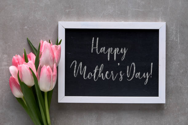 """greeting """"happy mother's day!"""" on blackboard with white tulips with pink stripes, flat lay on grey stone - mothers day stock pictures, royalty-free photos & images"""