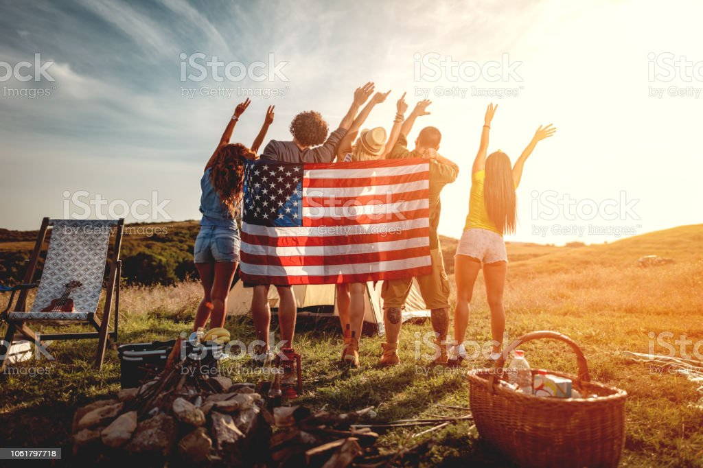 Greeting The Sun Happy young friends enjoy a sunny day in nature. They're looking at sun holding American flag and greeting, happy to be together. Adult Stock Photo