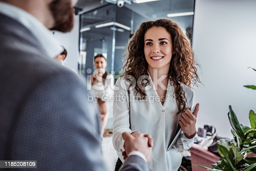Waist up shot of beautiful young woman shaking hand to stylish businessman in office setting