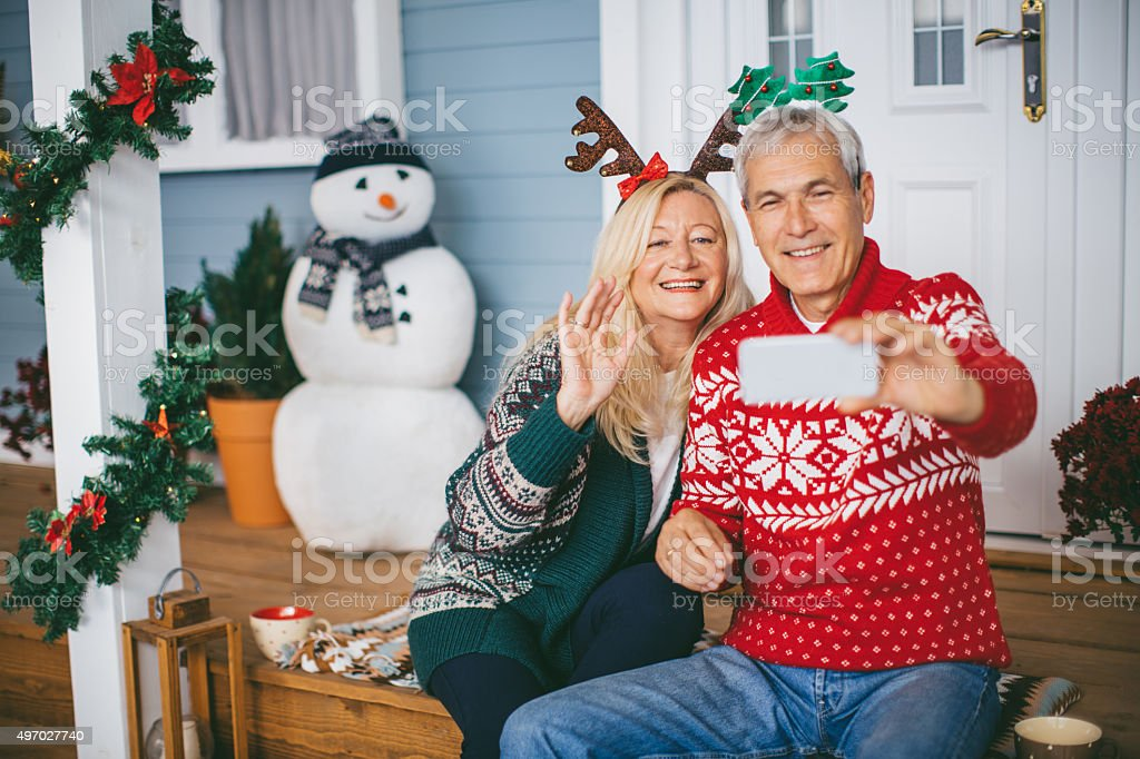 Mature couple in front of house for Christmas. Making selfie. They...