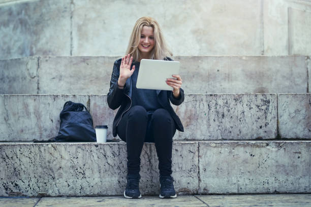 Greetings from half way around the world Shot of an attractive woman using a digital tablet to make a video call in the city long distance relationship stock pictures, royalty-free photos & images