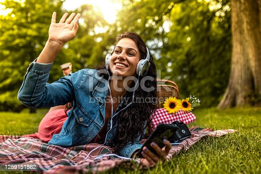 Pretty young woman lying on a picnic blanket at the park, listening to music and waving to someone from distance