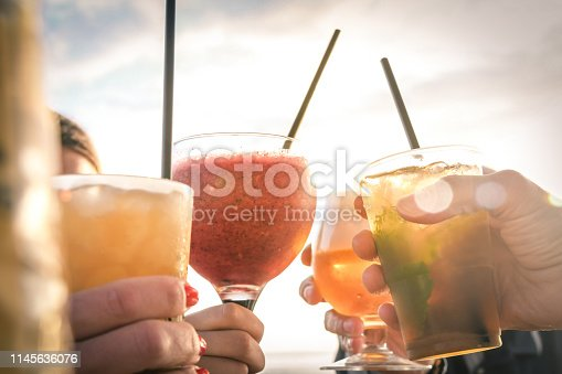 Greetings to best friends, group of friends enjoying evening drinks at the beach at sunset. Concept of vacation, carefree, end-of-day relaxation, celebration and well-being.