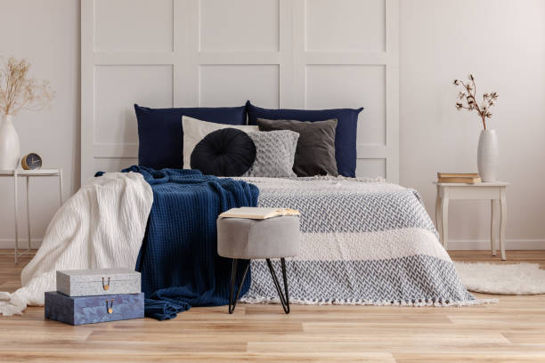 graue und blaue bettwäsche und decke auf bequemen king size-bett - marineblau schlafzimmer stock-fotos und bilder