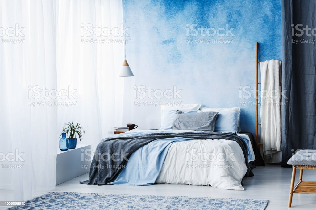 Grey and blue bedding on bed against ombre wall in minimal bedroom...