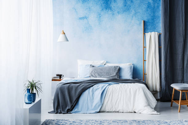 Grey and blue bedding on bed in spacious bedroom interior with ladder and plant stock photo