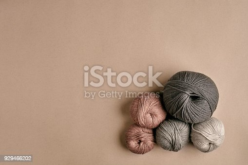istock Grey and brown knitting wool and knitting needles on beige background. Top view. Copy space 929466202