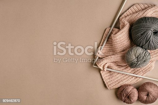 istock Grey and brown knitting wool and knitting on knitting needles on beige background. Top view. Copy space 929462870