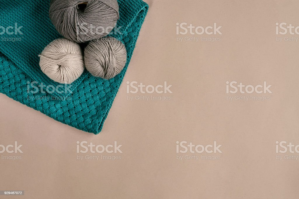Grey and turquoise knitting wool and knitting needles on beige background. Top view. Copy space stock photo