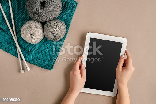 istock Grey and turquoise knitting wool, knitting needles and a tablet with a black screen on beige background. Top view. Copy space 929469090