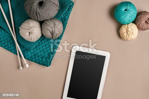 istock Grey and turquoise knitting wool, knitting needles and a tablet with a black screen on beige background. Top view. Copy space 929469148
