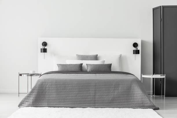 graue und weiße schlafzimmer innenraum - monitor wandhalterung stock-fotos und bilder