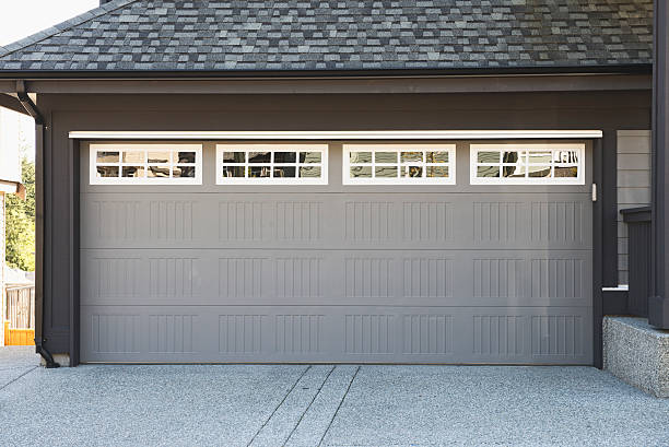 Grey and white garage door with windows stock photo