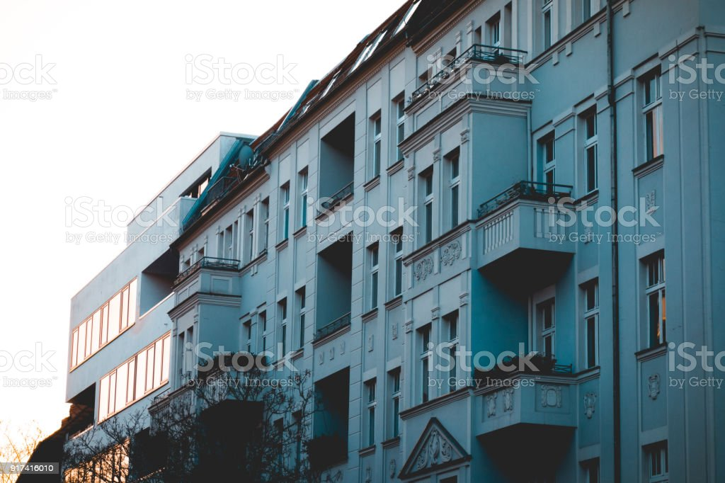 grey apartment houses with old and new facades stock photo