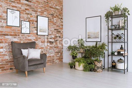 istock Grey armchair against brick wall 872873766