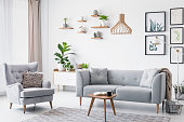 Grey armchair next to settee in bright living room interior with posters and wooden table. Real photo