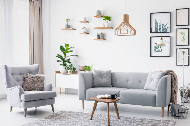 graue sessel neben sofa im hellen wohnzimmer interieur mit plakaten und holztisch. echtes foto - stuhlpolster stock-fotos und bilder