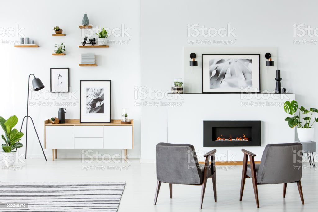 Grey armchairs in front of fireplace under poster in white apartment interior. Real photo