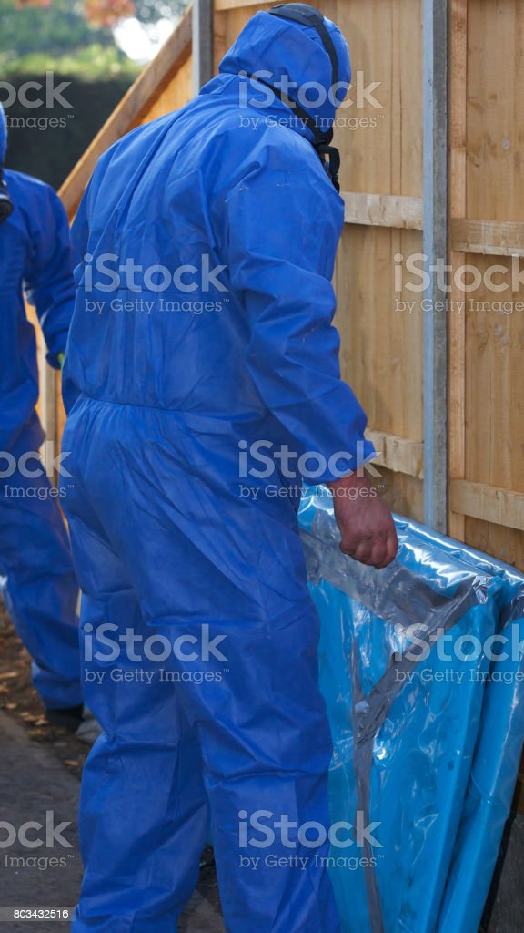 Grey asbestos being removed from a residental property by experts stock photo