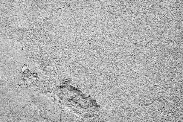 Grauer Hintergrund, graue Steinwand, Kalkwand. Strukturierte Betonwand mit beschädigungen und angebrpochenem Gemäuer mit rissen. – Foto