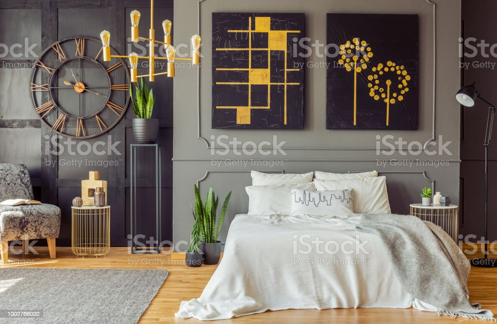 Grey Blanket On Bed Against The Wall With Black Posters In ...