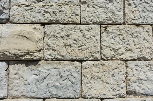 973649382 istock photo grey brick wall with big stones 828107240