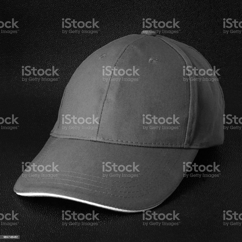 Grey cap on dark background. Template of baseball cap in side view. royalty-free stock photo