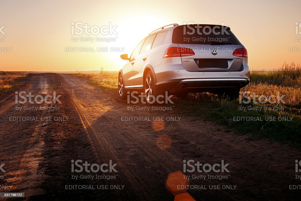 Grey car Volkswagen Passat stay on dirt road at sunset Saratov, Russia - June 02, 2014:  Volkswagen Passat car is parked at the dirt countryside road at sunset Backgrounds Stock Photo