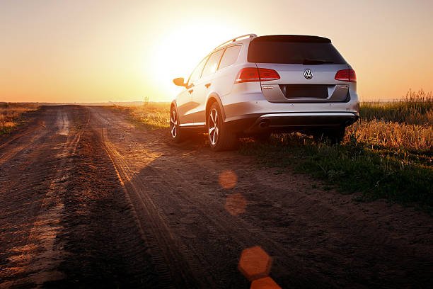 Grey car Volkswagen Passat stay on dirt road at sunset stock photo