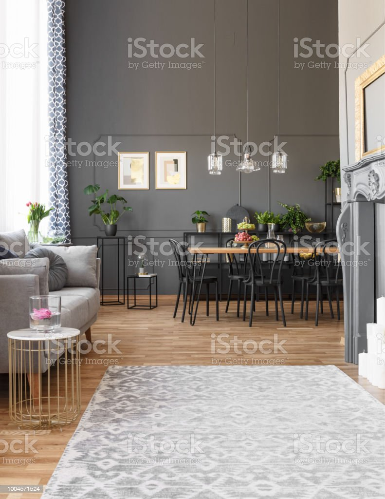 Grey carpet in spacious loft interior with sofa and black chairs at dining table under lamps. Real photo stock photo