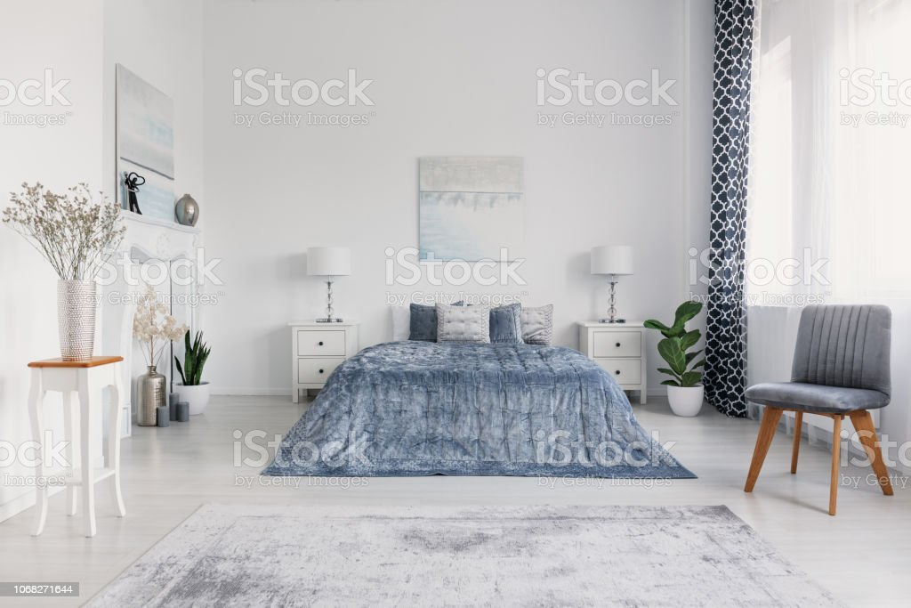 Grey Chair Next To Blue Bed In White Bedroom Interior With Posters And  Lamps On Cabinets Real Photo Stock Photo - Download Image Now