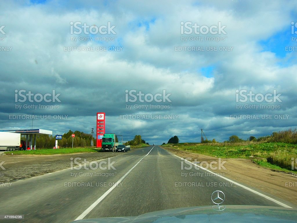 Grey clouds, highway and Mercedes sign on the hood royalty-free stock photo