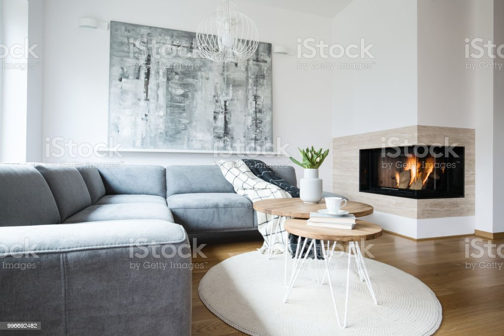 Grey corner settee with blankets standing in white Nordic living room interior with fresh tulips, books and tea cup on hairpin tables, abstract painting and fireplace