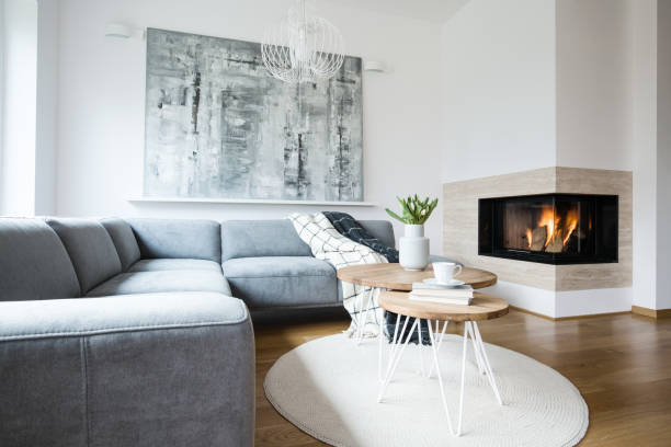 grey corner settee with blankets standing in white nordic living room interior with fresh tulips, books and tea cup on hairpin tables, abstract painting and fireplace - prodotto per l'igiene personale foto e immagini stock