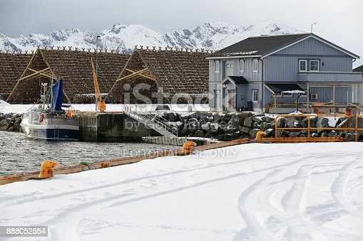 Laukvik, Austvagoya island, Norway-March 1, 2016: Fishing villages in the Lofoten islands show the adaptation of the local architecture to the environment and the materials available in the area as does this grey painted wooden cottage. Blue fishing boat with blue sail moored at the dock-huge hjells or A framed racks for stockfish drying-mounts of Gimsoya island in back. Vagan kommune-Lofoten archipelago.