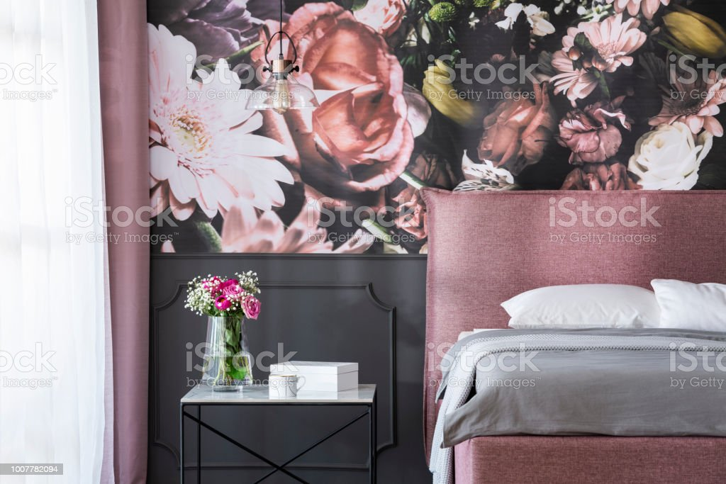 Grey Cushions On Pink Bed Next To Table With Flowers In Bedroom ...