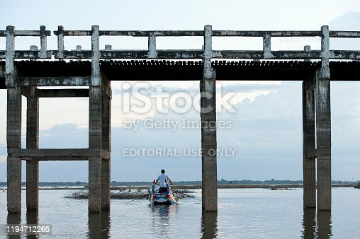 Boating, Ubein Bridge, Mandalay, Myanmar. A lethargic boatman rows his tourist boat through the arches of the teak bridge with tourists on board during a grey day on the lake, Ubein Bridge, Mandalay, Myanmar