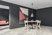 Corner of modern gray dining room with wooden floor, round table with grey chairs and abstract picture and living room with red sofa in background. 3d rendering