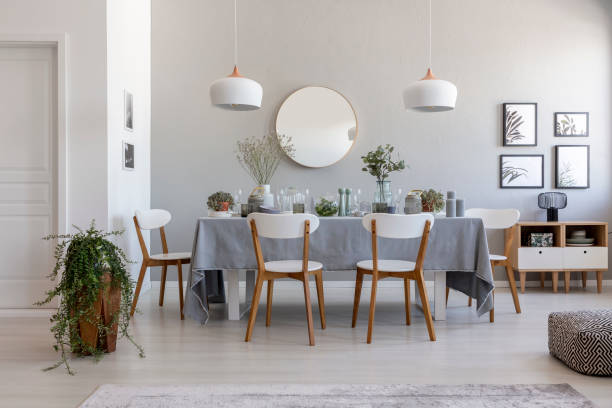 Grey dining room interior with a table, chairs and plant. Idea for a dinner stock photo