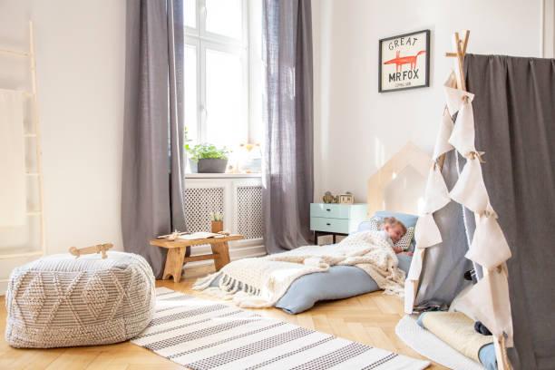 graue vorhänge am fenster und hocker auf teppich in jungen schlafzimmer innenraum mit poster über blauen bett. echtes foto - fuchs kissen stock-fotos und bilder
