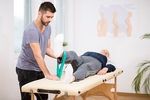 950649706 istock photo Grey elderly man lies on a physiotherapy table, and young doctor helps him during exercises 1147158904
