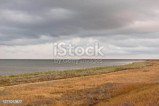 Grey high layered grey epic clouds above wild autumn yellow dry field with lake water line. Heaven cloudscape air view