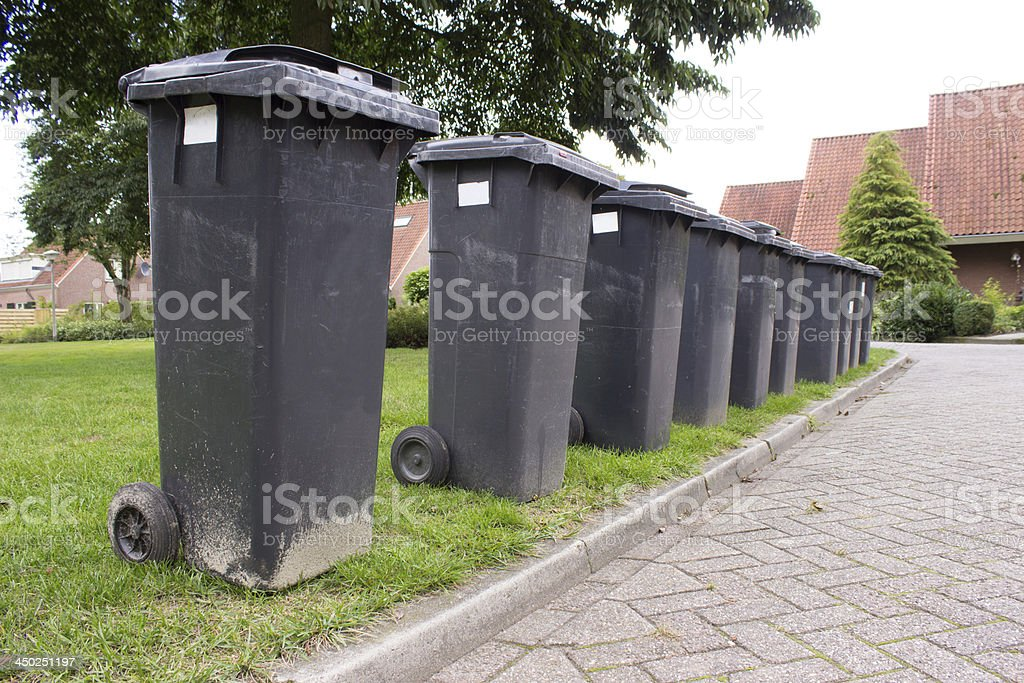 Grey garbage containers in a row stock photo