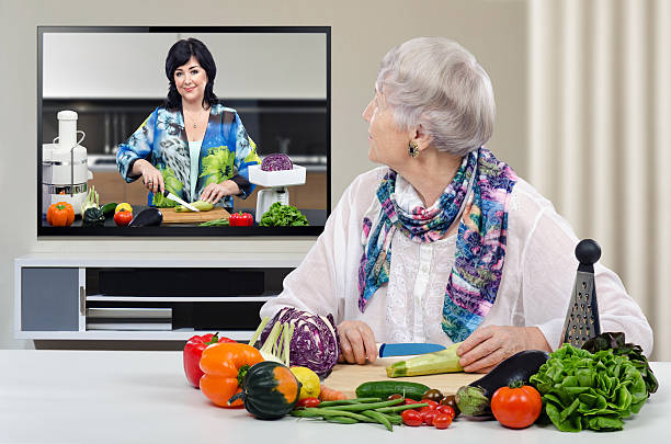Grey haired aged woman is cutting vegetables stock photo