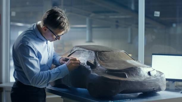 grauen haaren automobil-designer formt futuristisches automodell aus plastilin ton mit draht. er arbeitet in einem speziellen studio befindet sich in einem großen automobilwerk. - skulpturprojekte stock-fotos und bilder